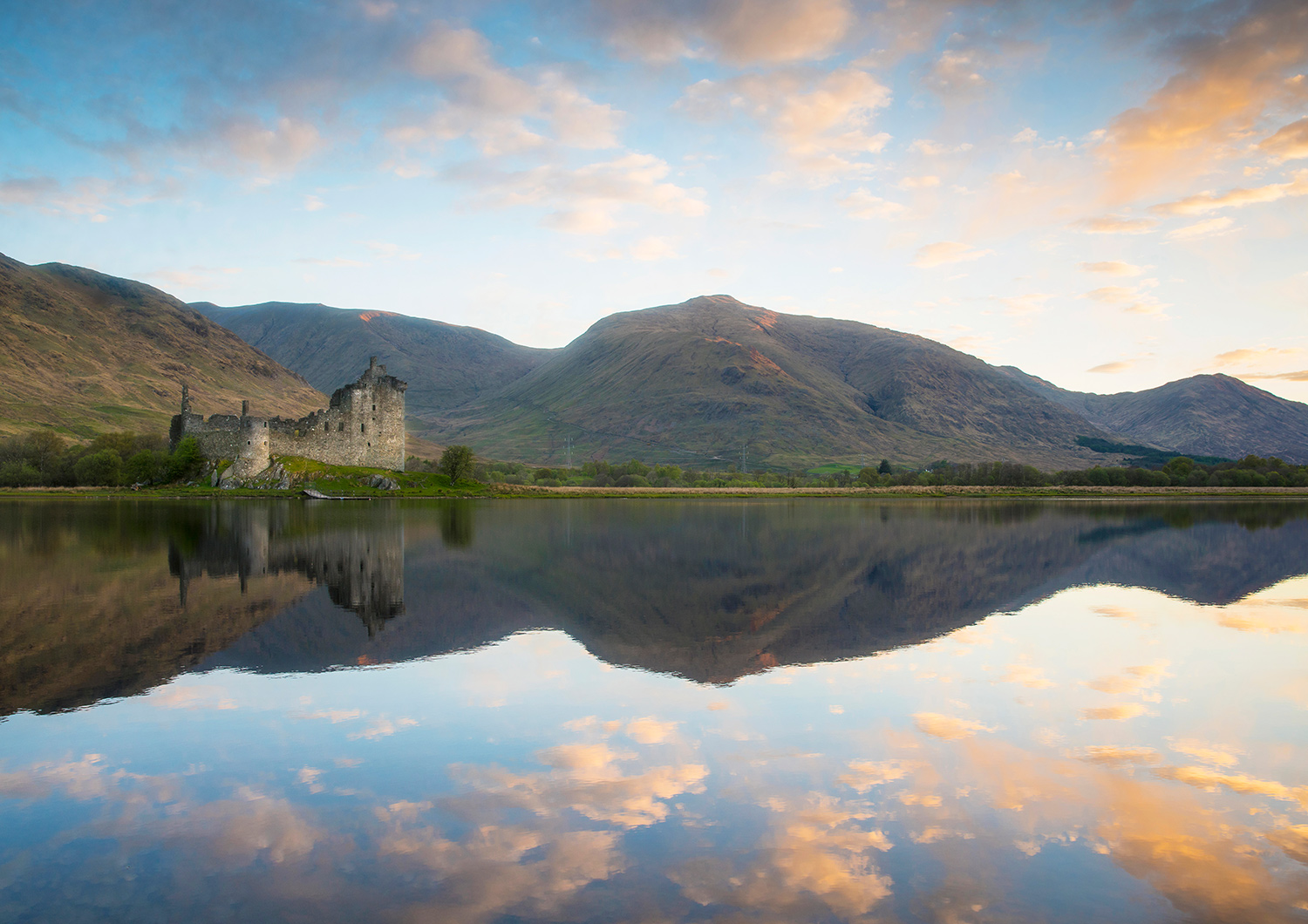 A caslte ruin is reflected on a calm loch, with hills beyond